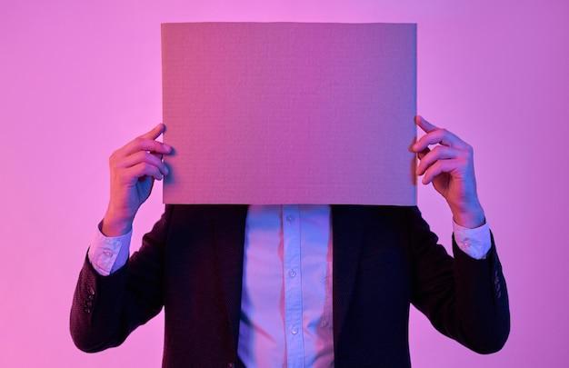 Jovem empresário atraente de terno preto e camisa branca com papelão nas mãos, espaço vazio para texto, isolado em rosa neon
