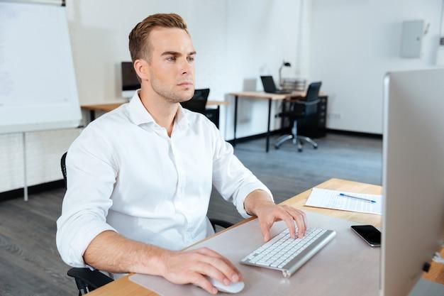 Jovem empresário atraente e focado, sentado no escritório e usando o computador