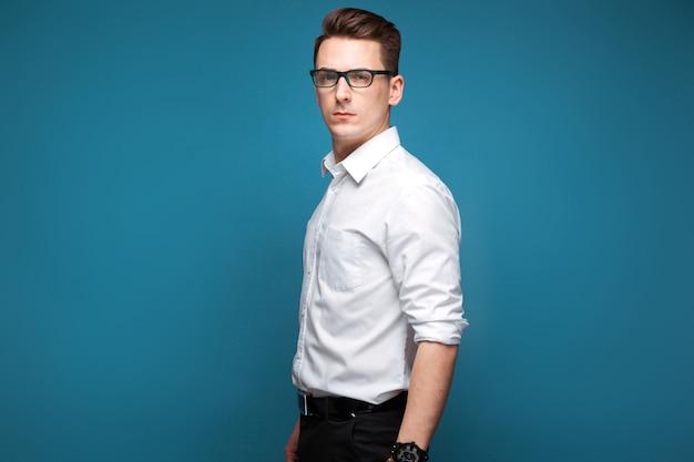Jovem empresário atraente em relógio caro, óculos escuros e camisa branca