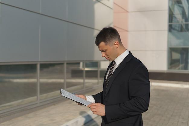 Jovem empresário atraente em terno formal fica no contexto de um prédio de escritórios na cidade e olha para documentos em um dia ensolarado