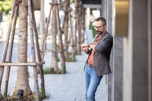 Jovem empresário atraente em um terno elegante, olhando para o relógio
