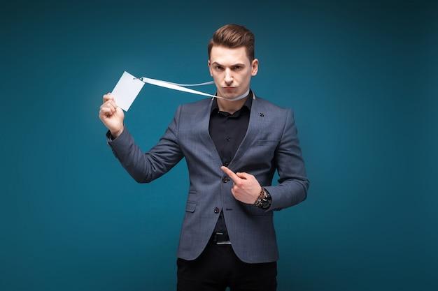 Jovem empresário atraente na jaqueta cinza com cartão de identificação em branco