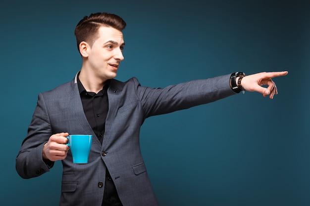 Jovem empresário atraente na jaqueta cinza e camisa preta segurar copo azul
