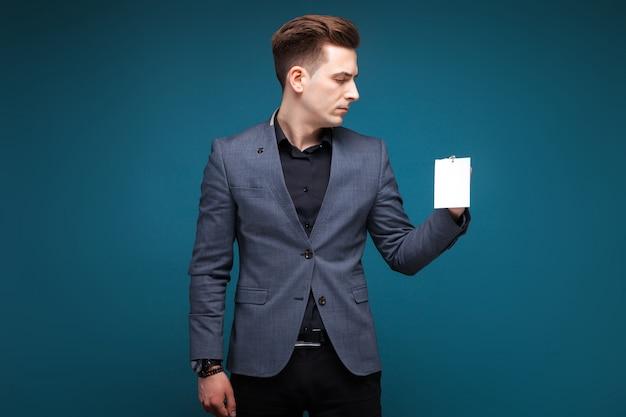 Jovem empresário atraente na jaqueta cinza, relógio caro, camisa preta e cartão em branco branco