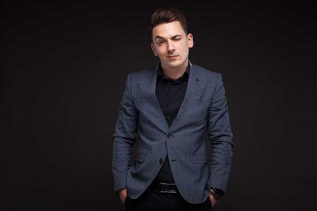 Jovem empresário atraente na jaqueta cinza, relógio caro e camisa preta, fundo preto