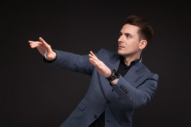 Jovem empresário atraente na jaqueta cinza, relógio caro e camisa preta