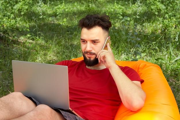 Jovem empresário atraente no sofá laranja do ar está trabalhando com o notebook e falando no celular na natureza.