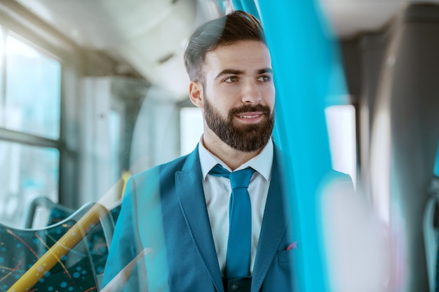 Jovem empresário atraente sorridente em terno azul, sentado em ônibus público e desviar o olhar.