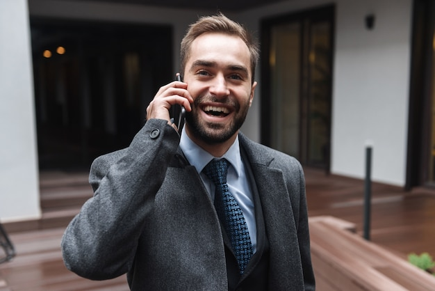 Jovem empresário atraente vestindo terno caminhando ao ar livre, usando telefone celular, conversando