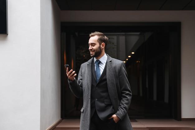 Jovem empresário atraente vestindo terno e caminhando ao ar livre, usando telefone celular