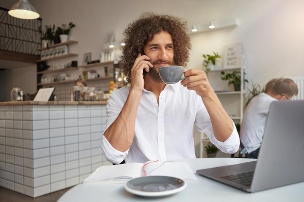 Jovem empresário barbudo atraente com cabelo longo cacheado posando sobre o interior do café, segurando uma xícara de café e olhando pela janela com um sorriso sincero, usando o laptop para trabalho remoto
