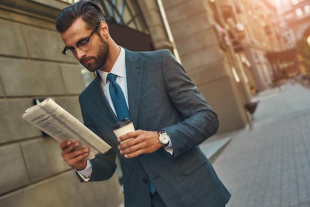 Jovem empresário barbudo bonito em óculos, lendo jornal e segurando uma xícara de café enquanto
