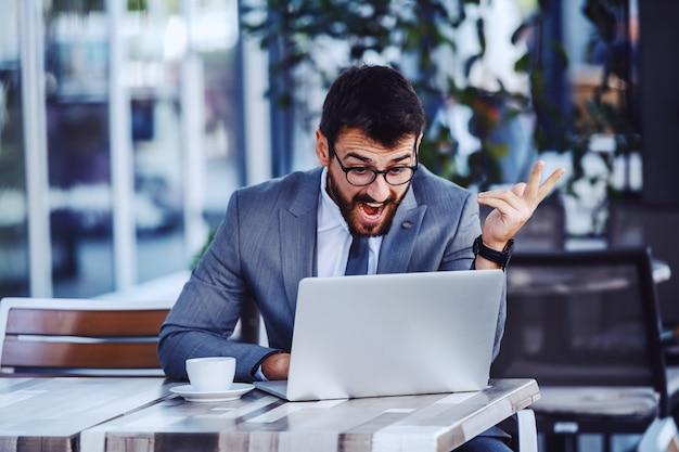 Jovem empresário barbudo caucasiano irritado de terno e óculos, tendo a vídeo chamada sobre o laptop enquanto está sentado no terraço do café.