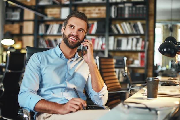 Jovem empresário barbudo com roupa formal falando com o cliente por telefone e sorrindo