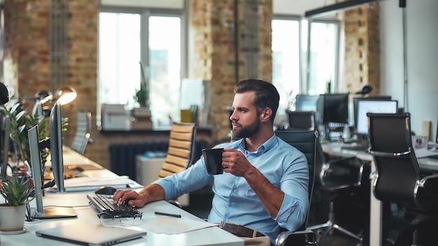 Jovem empresário barbudo com roupa formal segurando uma xícara de café e olhando para o computador