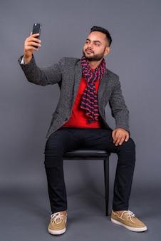 Jovem empresário barbudo contra cinza