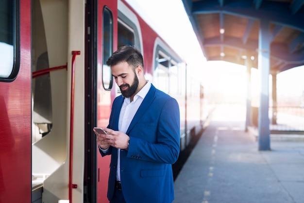 Jovem empresário barbudo em um terno elegante, esperando o trem do metrô chegar ao trabalho e usando seu smartphone