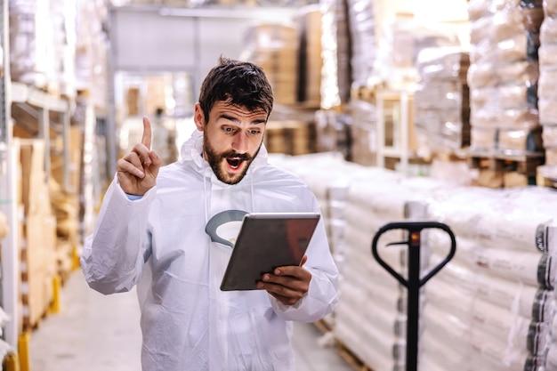 Jovem empresário barbudo inovador em uniforme estéril segurando e olhando para o tablet e tendo uma ideia de como resolver o problema salarial. o vírus corona covid 19 conceito de surto.