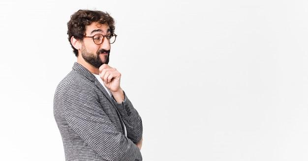 Jovem empresário barbudo louco contra a parede do espaço de cópia