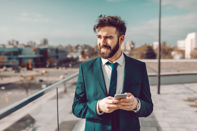 Jovem empresário barbudo pensativo caucasiano com roupa formal, usando telefone inteligente no telhado.