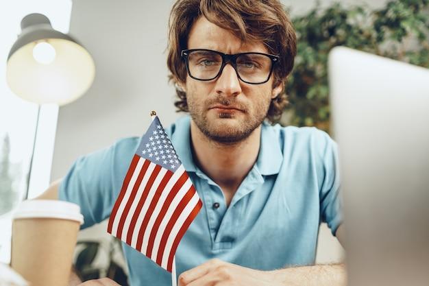 Jovem empresário barbudo sentado à mesa com o laptop e a bandeira americana