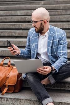 Jovem empresário barbudo sentado em degraus usando laptop e olhando para seu screenhipster homem está trabalhando em um blog, conversando online, verificando e-mail