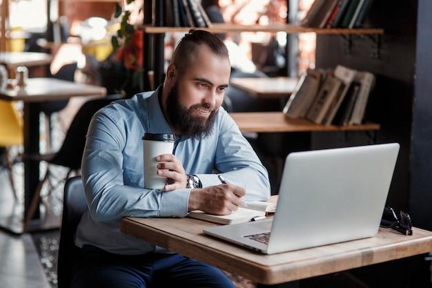 Jovem empresário barbudo sério trabalhando no computador na mesa, bebendo café. homem analisa informações