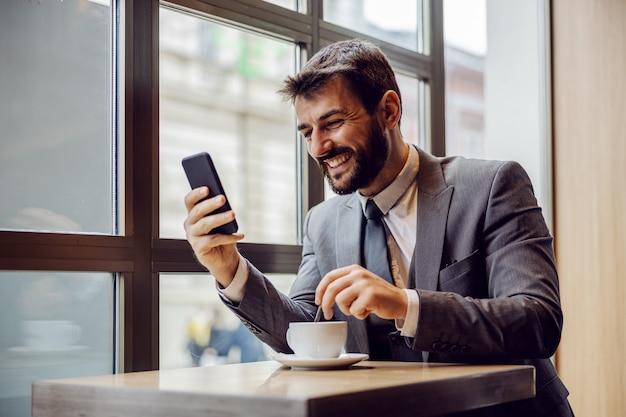 Jovem empresário barbudo sorridente, sentado na cafeteria, lendo algo engraçado no telefone inteligente e mexendo o café.