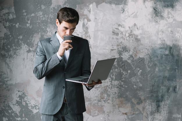 Jovem empresário bebendo café enquanto olha para laptop contra uma parede velha