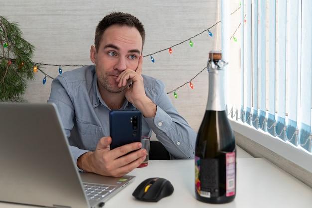 Jovem empresário bebendo de estresse. alcoolismo no local de trabalho. um funcionário cansado ou doente olha para uma garrafa de champanhe, quer comemorar o ano novo ou o natal
