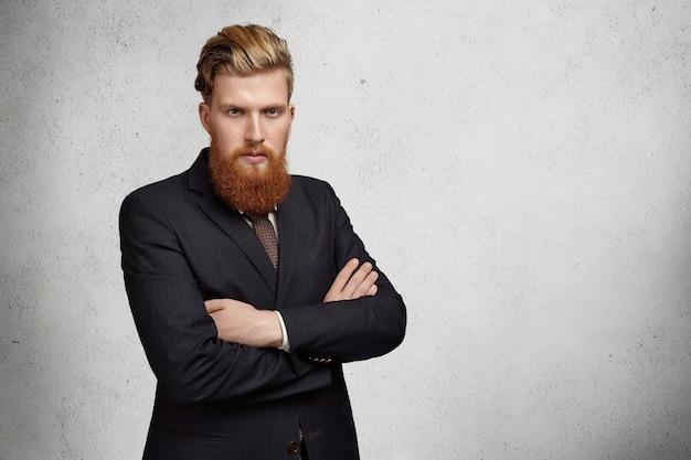 Jovem empresário bem-sucedido e confiante ou trabalhador de escritório com barba espessa e corte de cabelo elegante, vestindo terno e em pé com os braços cruzados contra a parede com espaço de cópia para sua informação