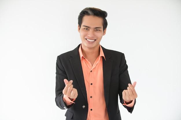 Jovem empresário bem sucedido fazendo um gesto de dinheiro