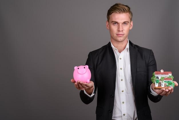 Jovem empresário bonitão com cabelos loiros, vestindo terno na parede cinza