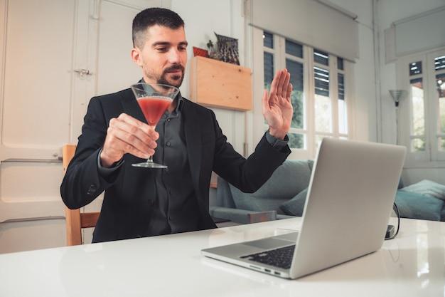 Jovem empresário bonitão com um coquetel em uma videochamada online