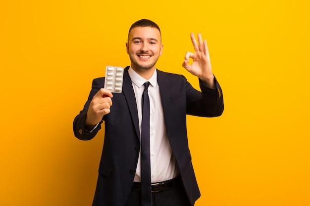 Jovem empresário bonitão contra parede plana com cápsulas de comprimidos