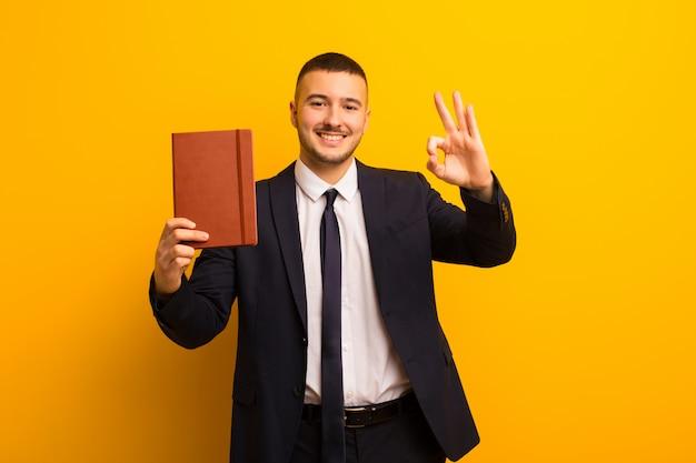 Jovem empresário bonitão contra um fundo liso com um livro diário