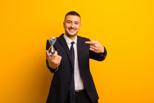 Jovem empresário bonitão contra um fundo liso com um relógio de areia