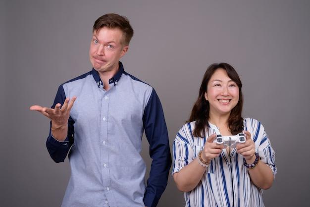 Jovem empresário bonitão e madura empresária asiática