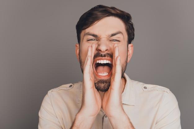 Jovem empresário bonitão gritando para anunciar uma grande notícia