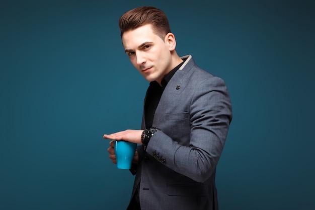 Jovem empresário bonitão na jaqueta cinza e camisa preta segurar copo azul