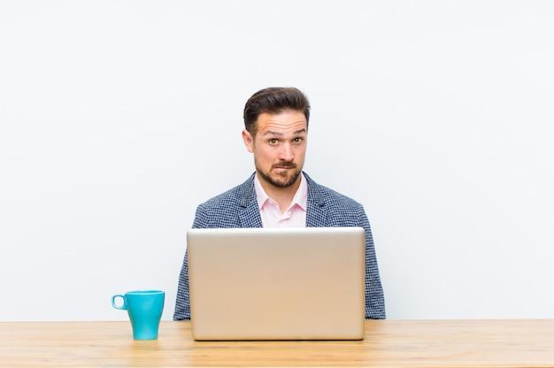 Jovem empresário bonitão olhando intrigado e confuso, mordendo o lábio com um gesto nervoso, sem saber a resposta para o problema