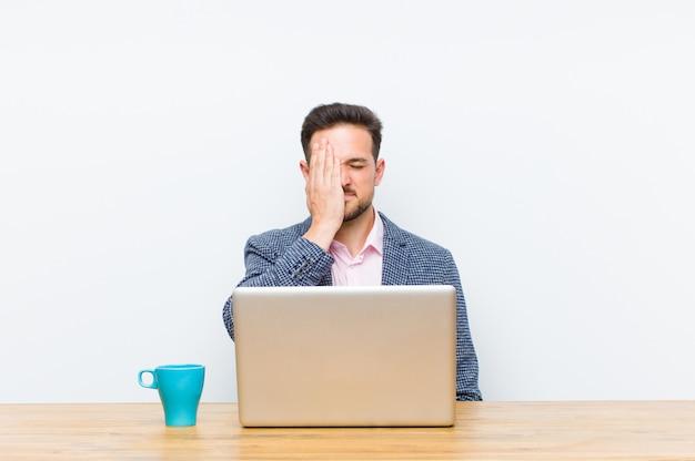 Jovem empresário bonitão olhando sonolento, entediado e bocejando, com dor de cabeça e uma mão cobrindo metade do rosto