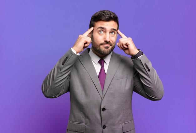 Jovem empresário bonitão parecendo concentrado e pensando seriamente em uma ideia, imaginando uma solução para um desafio ou problema