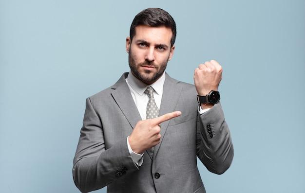 Jovem empresário bonitão parecendo impaciente e zangado, apontando para o relógio, pedindo pontualidade, quer ser pontual