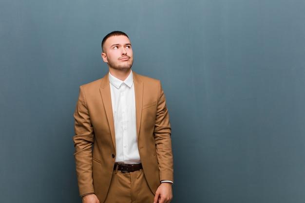 Jovem empresário bonitão parecendo perplexo e confuso, pensando ou tentando resolver um problema ou pensando contra uma parede plana