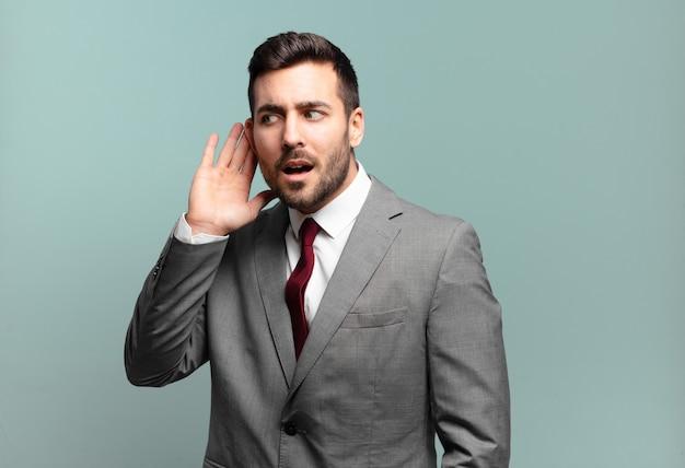Jovem empresário bonitão parecendo sério e curioso, ouvindo, tentando ouvir uma conversa secreta ou fofoca, espionando