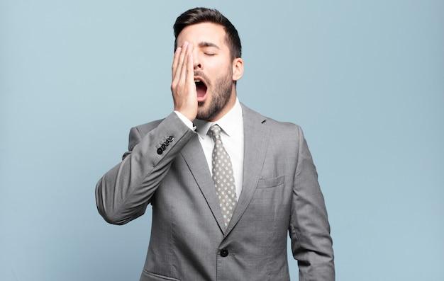 Jovem empresário bonitão parecendo sonolento, entediado e bocejando, com dor de cabeça e uma das mãos cobrindo metade do rosto