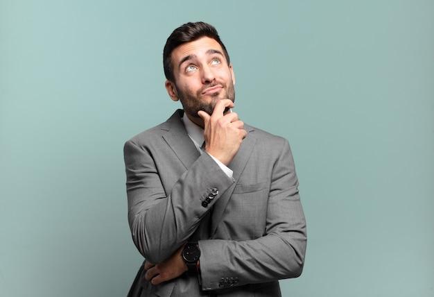 Jovem empresário bonitão pensando, se sentindo duvidoso e confuso, com diferentes opções, imaginando qual decisão tomar