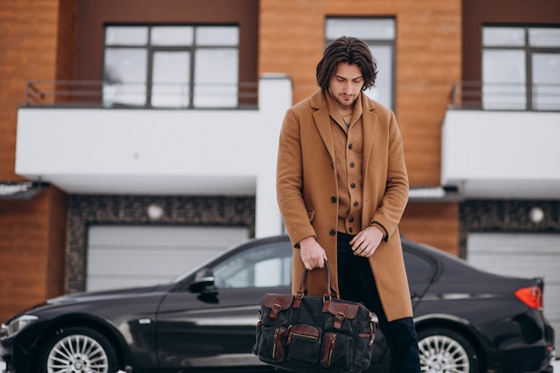 Jovem empresário bonitão saindo de casa em seu carro