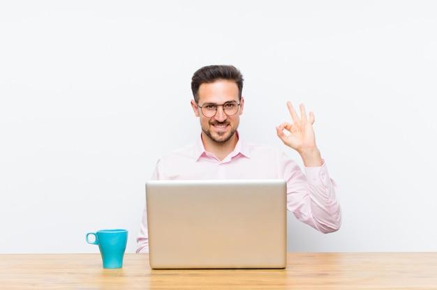 Jovem empresário bonitão se sentindo feliz, relaxado e satisfeito, mostrando aprovação com gesto bem, sorrindo